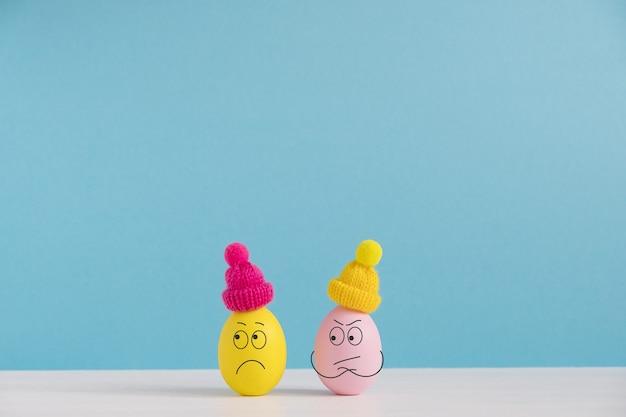 Osterferienkonzept mit niedlichen eiern mit lustigen gesichtern. unterschiedliche emotionen und gefühle. paar im streit Premium Fotos