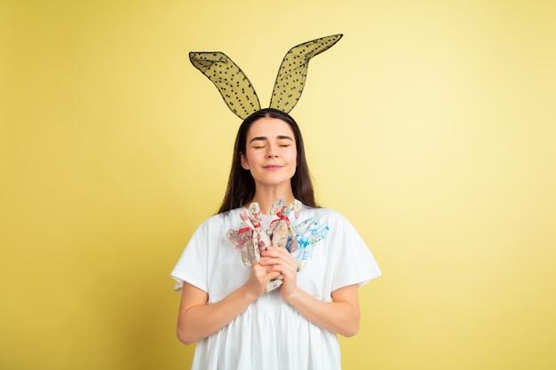 Osterhasenfrau mit hellen emotionen auf gelber wand Kostenlose Fotos