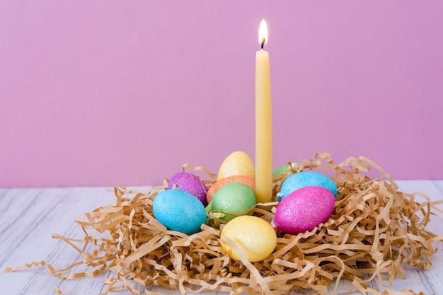 Osterkarte mit nest, farbigen eiern und brennender wachskerze auf lila pastellhintergrund Premium Fotos