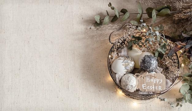 Osterkomposition mit dekorativen eiern in einem korb auf einem strukturierten hellen oberflächenkopierraum. Kostenlose Fotos