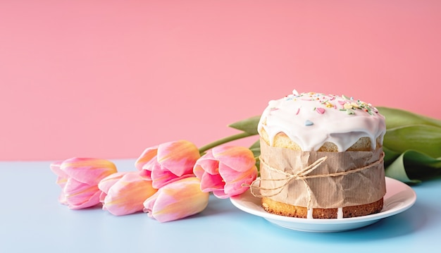Osterkonzept. osterkuchen mit tulpen auf vorderansicht des rosa und blauen hintergrunds mit kopienraum Premium Fotos