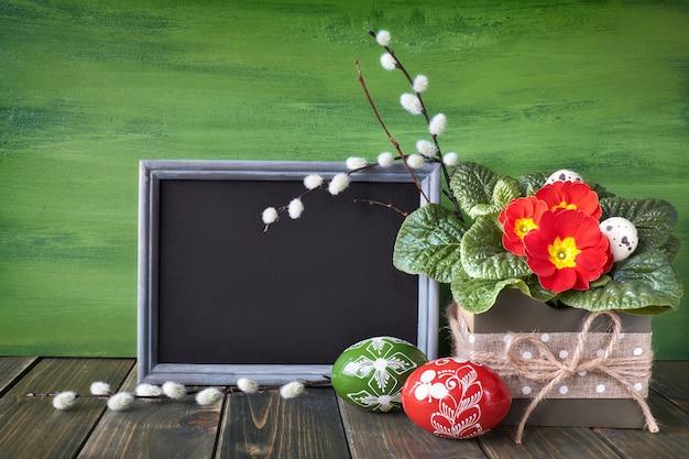 Osterkorb mit gemalten ostereiern und roter primel-topfblume auf rustikalem hölzernem hintergrund Premium Fotos
