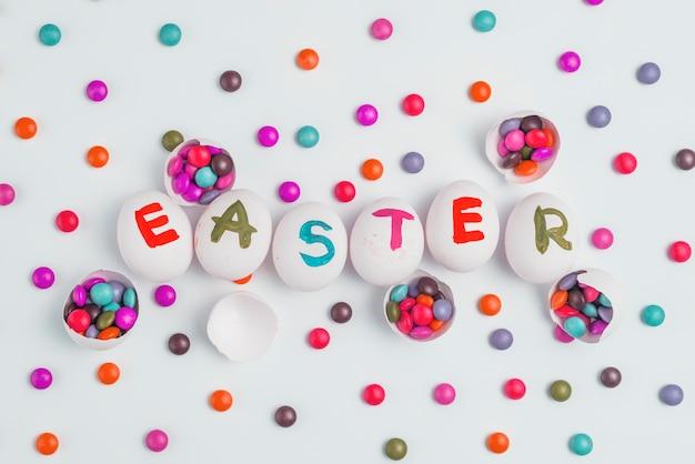 Ostern-aufschrift auf eiern mit süßigkeiten auf tabelle Kostenlose Fotos