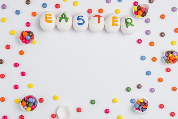 Ostern-aufschrift auf eiern mit süßigkeiten auf weißer tabelle Kostenlose Fotos