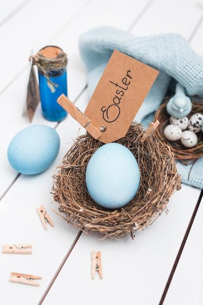Ostern-aufschrift mit hellem ei im nest Kostenlose Fotos
