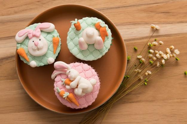 Ostern. draufsicht einer schönen rustikalen platte mit 3 ostern-kleinen kuchen im häschenkopf und im häschenendstück auf die oberseite. Premium Fotos