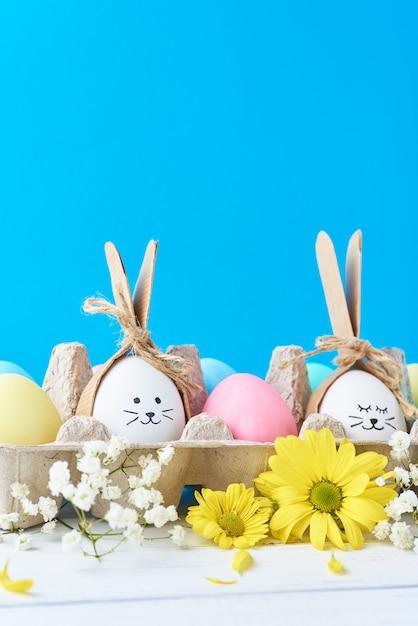 Ostern färbte eier im papierbehälter mit decorationd auf einem blauen hintergrund Premium Fotos