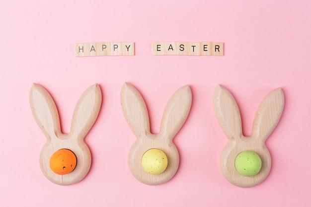 Ostern-feiertagsrosahintergrund mit farbigen eiern in den häschenohren formte eierbecher. frohe ostern holzbuchstaben. flach legen Premium Fotos