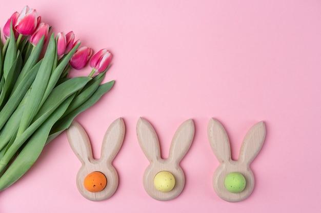 Ostern-feiertagsrosahintergrund mit farbigen eiern in den häschenohren formte eierbecher, rosa blumentulpe. flach legen Premium Fotos