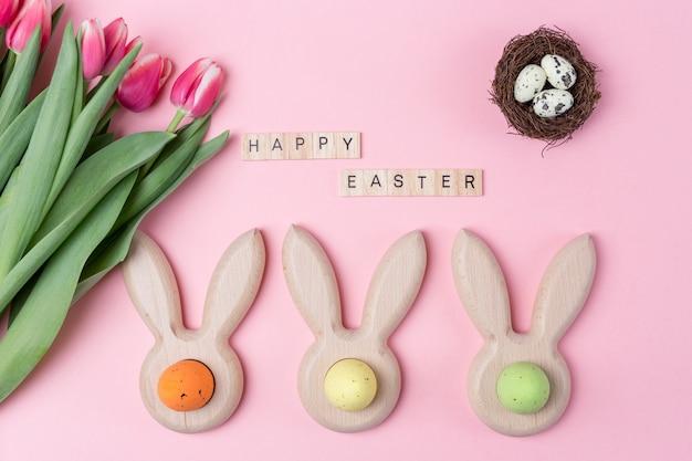 Ostern-feiertagsrosahintergrund mit farbigen eiern in den häschenohren formte eierbecher, rosa blumentulpe Premium Fotos