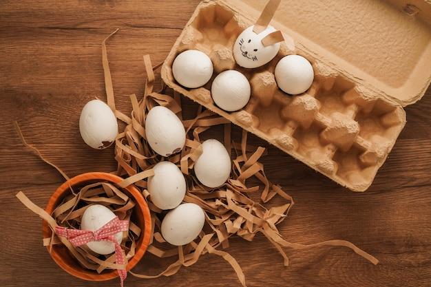 Ostern, gebundenes ei mit rotem band in der holzschale, gemaltes ei wie kaninchengesicht in eierablage auf holztisch Premium Fotos