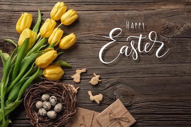 Ostern-hintergrund mit bunten eiern und gelben tulpen auf holztisch, draufsicht Premium Fotos
