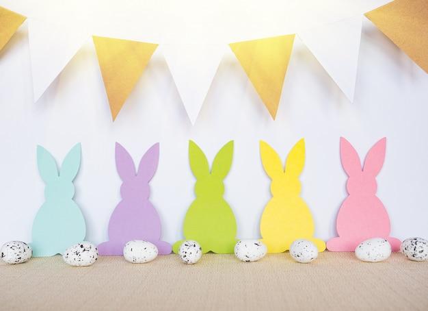 Ostern-hintergrund mit eiern, kaninchen und girlandenflaggen Premium Fotos