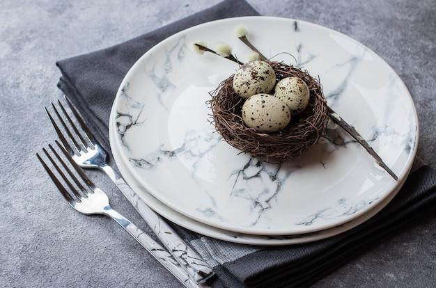 Ostern-hintergrund mit marmorplatten, gabeln, geschirrtuch und ostern-dekor Premium Fotos