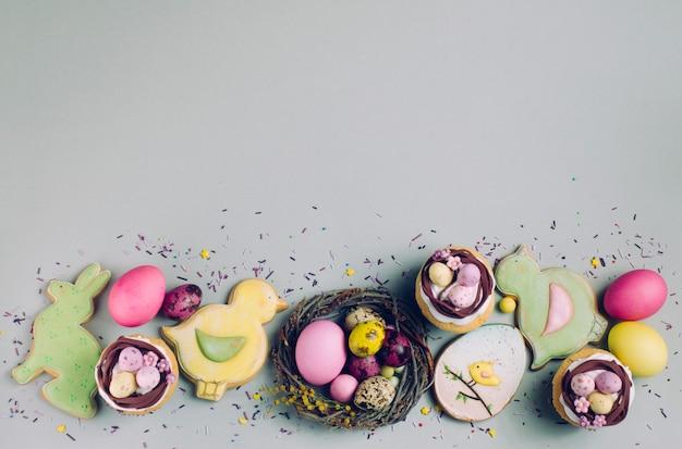 Ostern-kleine kuchen, gemalte eier und ingwerbrote auf grauem hintergrund Premium Fotos
