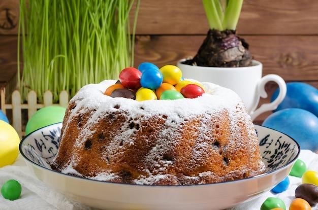 Ostern-kleiner kuchen mit puderzucker und gebäck auf hölzernem rustikalem hintergrund Premium Fotos