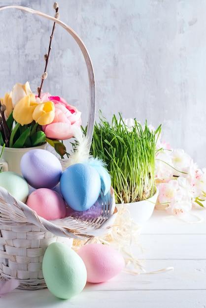 Ostern-korb füllte mit bunten handgemalten ostereiern über einem hellen hintergrund Premium Fotos
