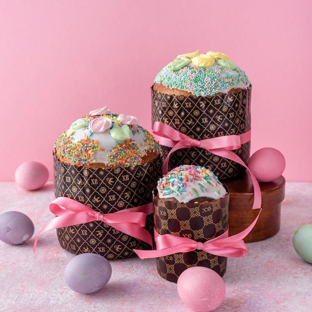 Ostern-kuchen, gemalte eier auf rosa hintergrund. Premium Fotos