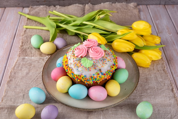 Ostern-kuchen, gemalte eier mit tulpen auf einem hölzernen alten rustikalen hintergrund. Premium Fotos