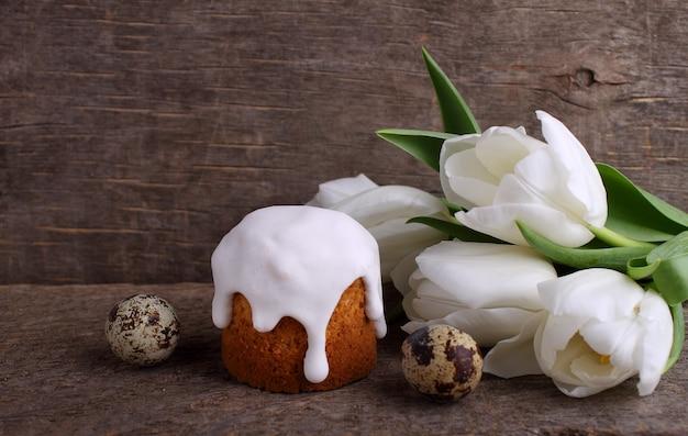 Ostern-kuchen, weiße tulpen, wachteleier auf einem hölzernen rustikalen hintergrund. Premium Fotos