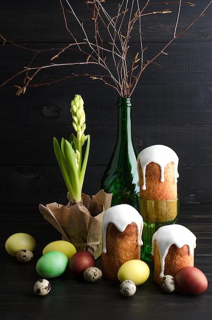 Ostern-stillleben ostern-kuchen und -eier auf einem dunklen, hölzernen hintergrund. Premium Fotos