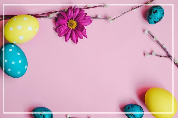 Ostern-wachteleier, frühlingsblumen und weide auf rosa hintergrund Premium Fotos