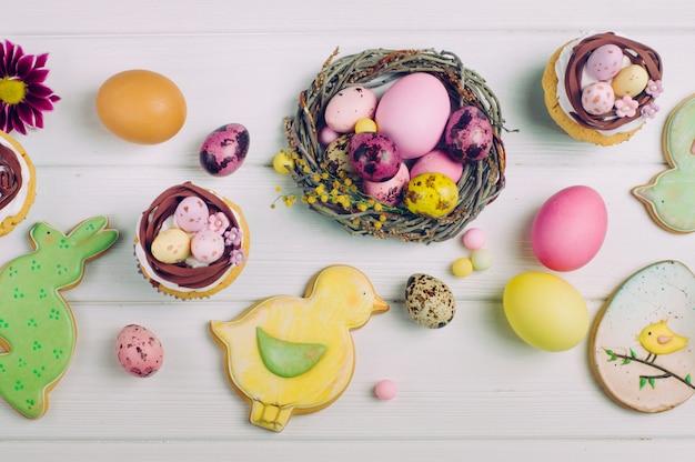Osternestkleine kuchen, gemalte eier und ingwerbrote auf hellem hölzernem hintergrund Premium Fotos