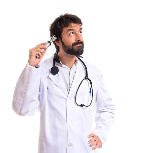 Otorhinolaryngologist mit seinem otoskop auf weißem hintergrund Kostenlose Fotos