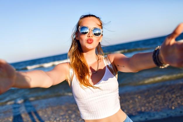 Outdoor-lifestyle-porträt des lustigen glücklichen mädchens, das allein zum ozean reist und selfie am strand, glückliche positive emotionen, gespiegelte sonnenbrille, weißes erntedach und rucksack, freude, bewegung macht. Kostenlose Fotos