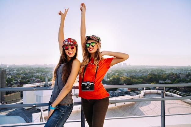 Outdoor-lifestyle-porträt von zwei ziemlich stilvollen besten freunden, die auf dem dach mit herrlichem blick auf die stadt posieren, legen ihre hände in die luft und schreien schreiend, werden verrückt und genießen ihre freiheit Kostenlose Fotos