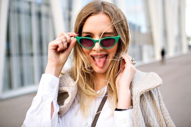 Outdoor-mode nahaufnahme porträt der atemberaubenden blonden geschäftsdame frau, lächelnd und vor der kamera, kaschmir mantel, vintage cat eye sonnenbrille, schmuck, weiche farben. Kostenlose Fotos