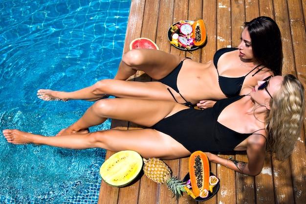 Outdoor-mode-porträt zu zwei hübschen freundinnen, die spaß beim legen und entspannen in der nähe der poolparty haben, süße tropische früchte, sexy bikini, sonnenbrille, firmenspaß halten, sonnenbaden bekommen. Kostenlose Fotos