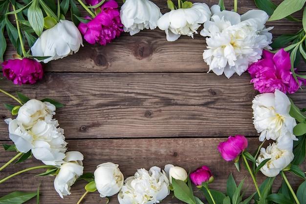 Ovaler rahmen der weißen und rosa pfingstrosen auf hölzernem hintergrund Premium Fotos