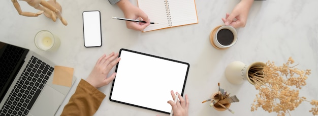 Overhead-aufnahme von geschäftsleuten, die auf ihrem projekt auf weißem schreibtisch brainstorming durchführen Premium Fotos