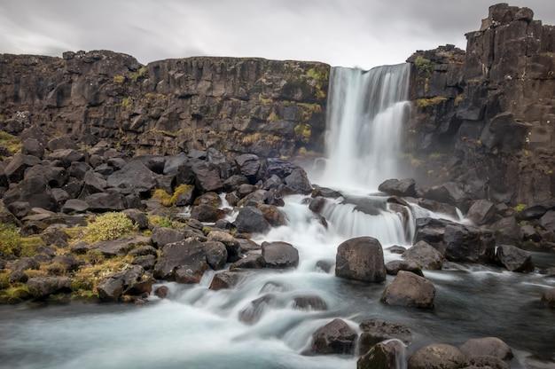 Oxararfoss wasserfall in thingvellir, island unter einem bewölkten himmel Kostenlose Fotos