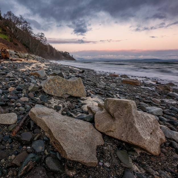 Ozeanwellen, die an land während des sonnenuntergangs abstürzen Kostenlose Fotos