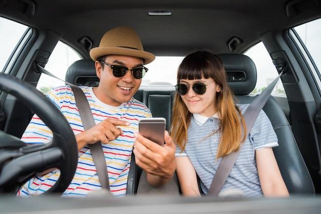 Paar asiatischer mann und frau, die im auto sitzen und telefon betrachten. reisekonzept. Premium Fotos