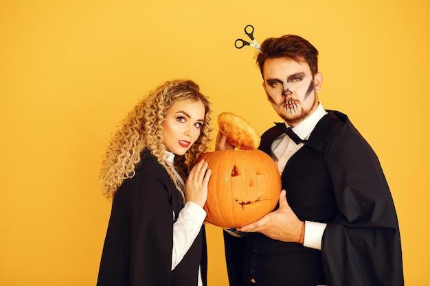 Paar auf gelbem grund. frau, die schwarzes kostüm trägt. dame mit halloween make-up. Kostenlose Fotos