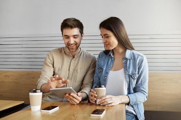 Paar begeisterte marketing-spezialisten, die im café am tisch sitzen, lächeln, kaffee trinken, über arbeit sprechen, digitale tablets und smartphones verwenden. Kostenlose Fotos