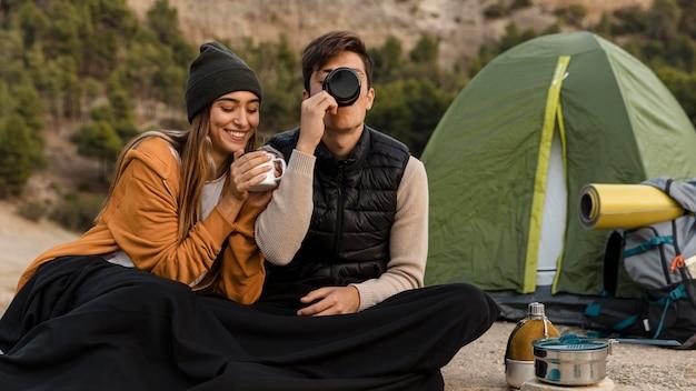 Paar camping und tee trinken zusammen Kostenlose Fotos