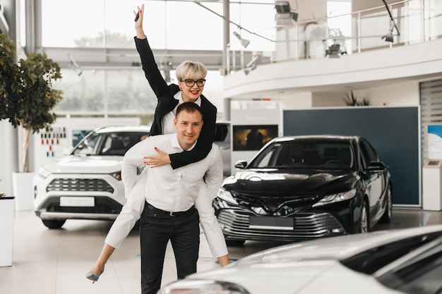 Paar das auto zu kaufen. paar in einem autosalon wählen sie ein automobil Premium Fotos