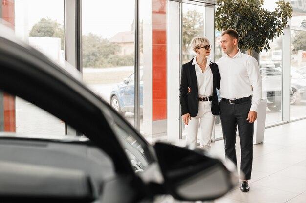 Paar das auto zu kaufen. paar in einem autosalon. Premium Fotos