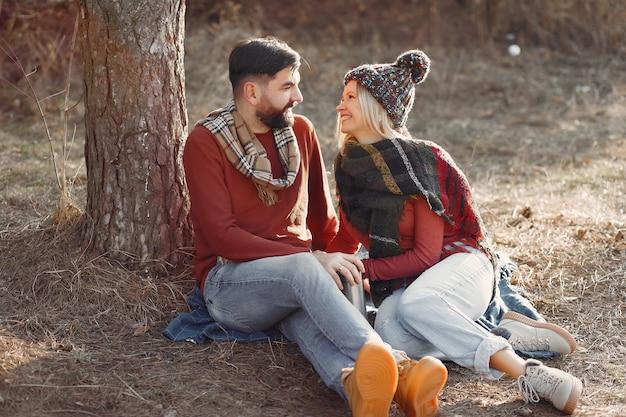 Paar, das durch einen baum in einem frühlingswald sitzt Kostenlose Fotos