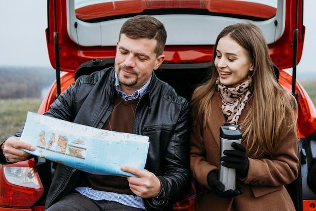 Paar, das eine karte im kofferraum des autos überprüft Kostenlose Fotos