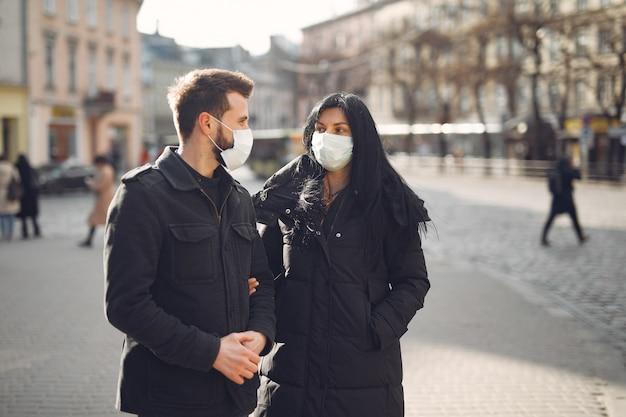 Paar, das eine schutzmaske trägt, die auf der straße steht Kostenlose Fotos