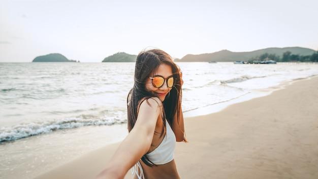 Paar, das hand am strand im sonnenuntergang hält Premium Fotos