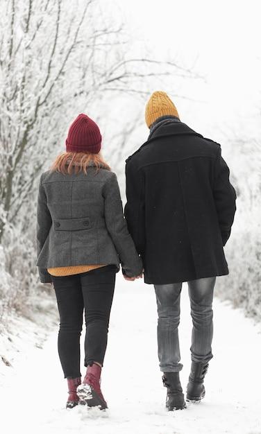 Paar, das im winter von hinten im freien geht Kostenlose Fotos