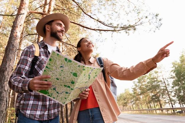 Paar, das in die gleichen richtungen schaut, während mann eine karte hält Kostenlose Fotos