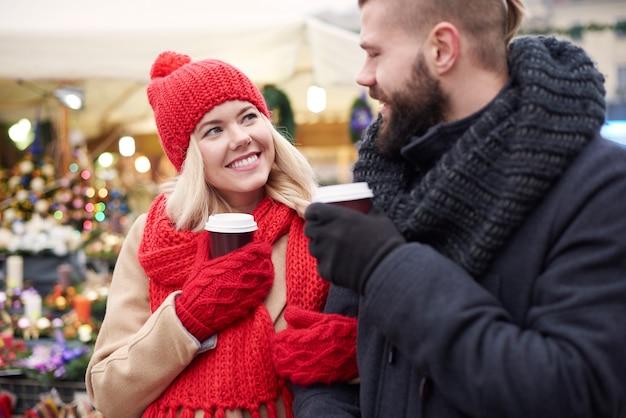 Paar, das kaffee auf weihnachtsmarkt trinkt Kostenlose Fotos