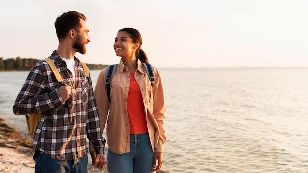 Paar, das sich beim spaziergang am meer ansieht Kostenlose Fotos